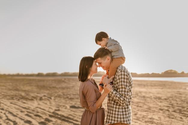Gelukkige familie wandelen op het zandstrand van de rivier. vader, moeder die zoontje op handen houdt en samen gaat. achteraanzicht. familiebanden concept.