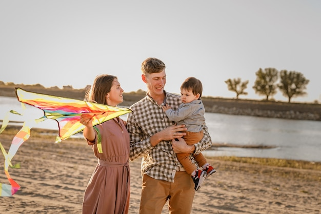 Gelukkige familie wandelen op zandstrand. vader, moeder zoontje op handen houden en spelen met vlieger.