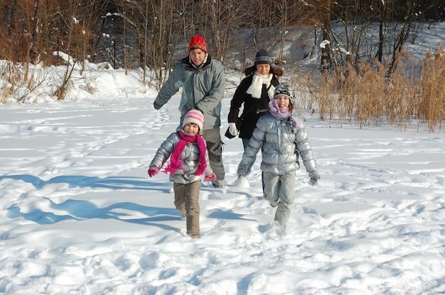Gelukkige familie wandelingen in de winter, plezier maken en buiten spelen met sneeuw op vakantie weekend