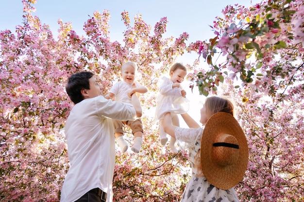 Gelukkige familie wandelingen in het park in de zomer tegen de achtergrond van een bloeiende appelboom