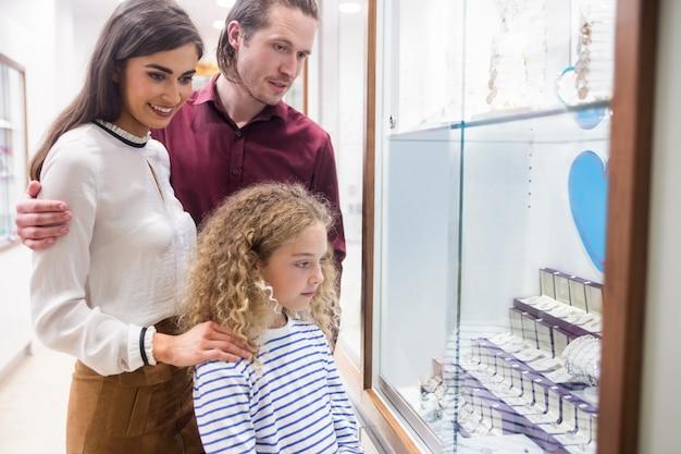 Gelukkige familie winkelen in juwelier winkel