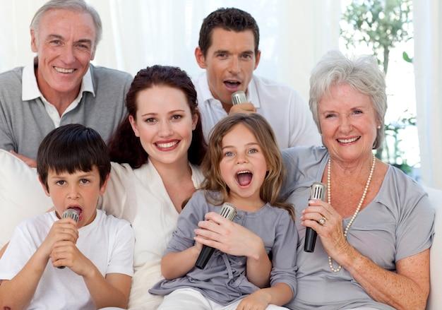 Gelukkige familie zingen karaoke in de woonkamer