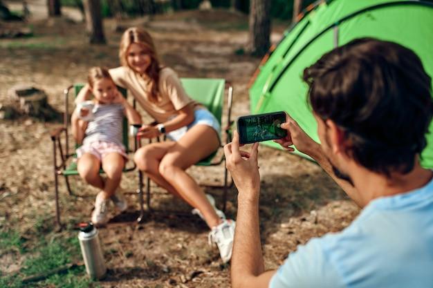 Gelukkige familie zitten bij het kampvuur in de buurt van de tent in het dennenbos voor het weekend. een man maakt een foto van zijn vrouw en dochter op zijn telefoon. kamperen, recreatie, wandelen.