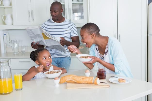 Gelukkige familie zitten en nemen ontbijt