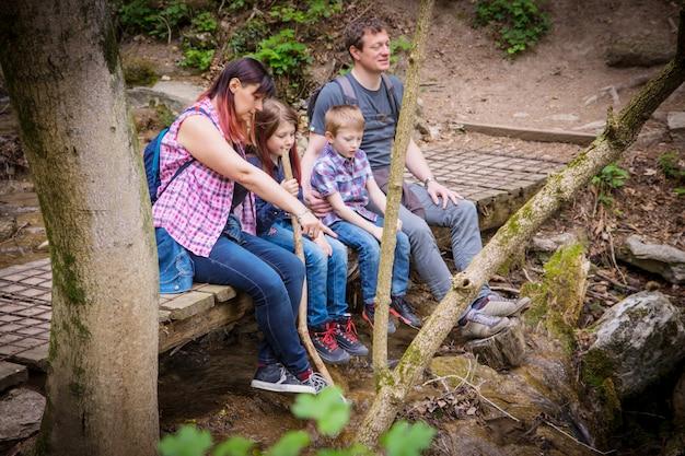 Gelukkige familie zitten op een houten brug in het midden van het bos