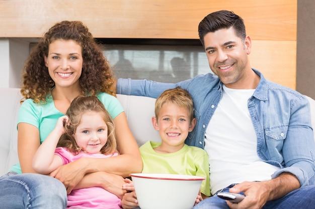 Gelukkige familie zittend op de bank tv kijken met popcorn