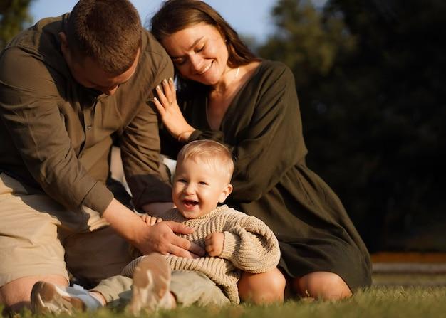 Gelukkige familie zittend op het gras in het park moeder zet hoofd op de schouder van echtgenoot babyjongen lachen ha