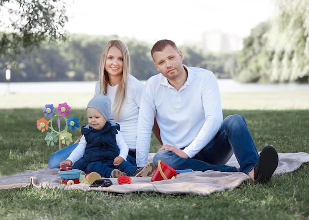 Gelukkige familie zittend op het gras in het park op een lentedag