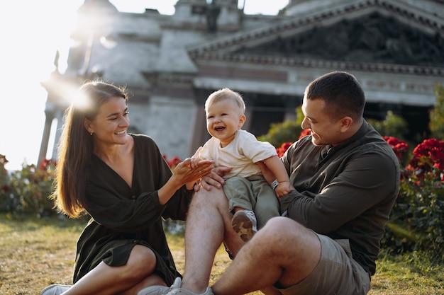 Gelukkige familie zittend op het gras voor st isaacs cathedral sint-petersburg