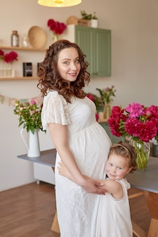 Gelukkige familie, zwangere vrouw met dochtertje in keuken met pioenrozen bloemen. relatie tussen ouders en kinderen. moederschap, zwangerschap, geluk concept.