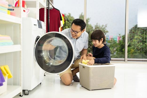Gelukkige familieman, vader, gezinshoofd en kind, zoon, kleine helper, hebben plezier en glimlachen terwijl ze de was doen met de wasmachine