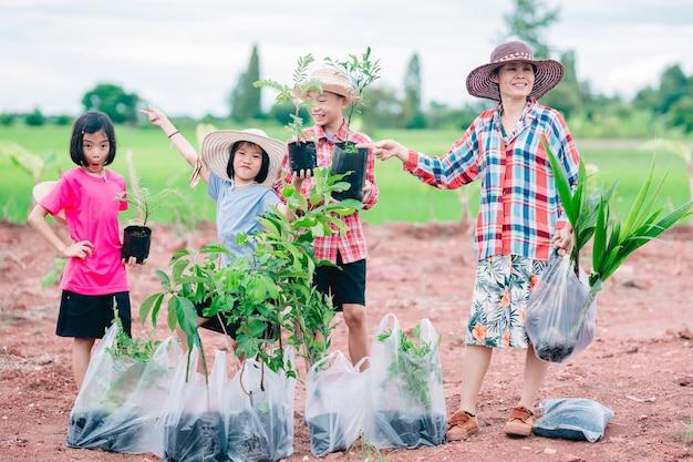 Gelukkige familiemensen die het zaaien van een boom houden voor het planten in de tuin op biologisch groen rijstveld