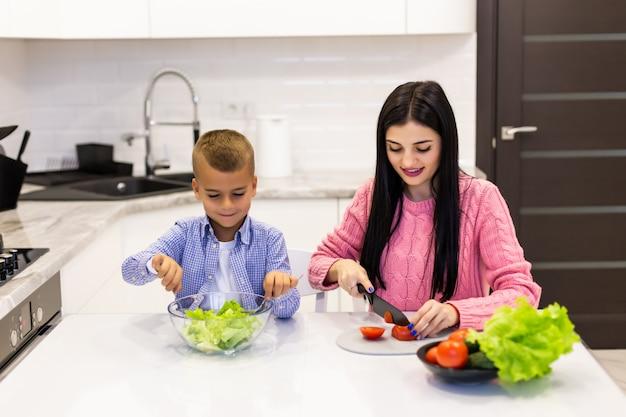 Gelukkige familiemoeder die met kindzoon plantaardige salade thuis voorbereiden