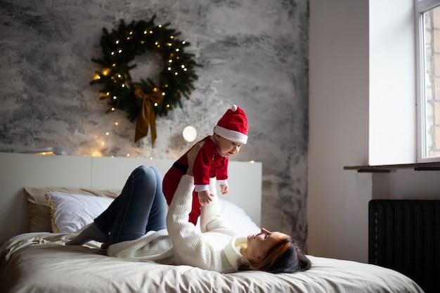 Gelukkige familiemoeder en baby zoontje spelen thuis op kerstvakantie. nieuwjaars vakantie.
