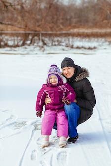 Gelukkige familiemoeder en de dochter van het babymeisje spelen die in de winter in openlucht lachen