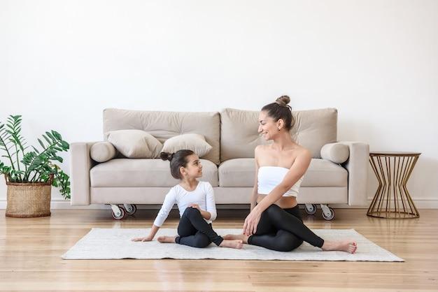 Gelukkige familiemoeder en dochter die thuis yoga doen