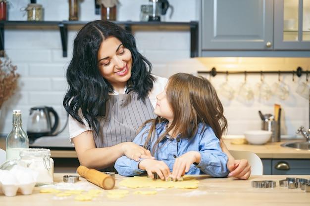 Gelukkige familiemoeder en dochter die zelfgemaakte koekjes samen in de keuken voorbereiden.