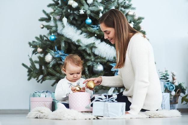 Gelukkige familiemoeder en kinddochter op kerstmisochtend bij de kerstboom met giften