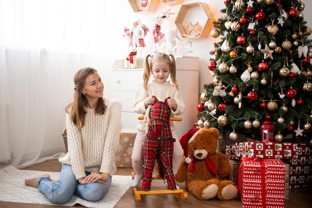 Gelukkige familiemoeder en kinddochter thuis dichtbij kerstboom en giftdozen