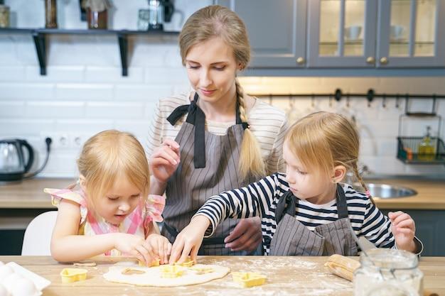 Gelukkige familiemoeder en twee leuke dochters die zelfgemaakte koekjes in de keuken voorbereiden.