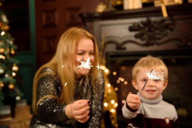 Gelukkige familiemoeder en zoon met sterretje dichtbij een kerstboom.