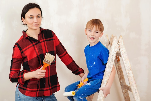 Gelukkige familiemoeder en zoon schilderen de muur