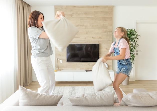 Gelukkige familiespellen, alleenstaande moeder en haar kindmeisje vechten tegen kussens en springen op de bank