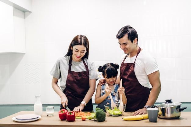 Gelukkige familievader en moeder met dochter die en maaltijd koken voorbereiden