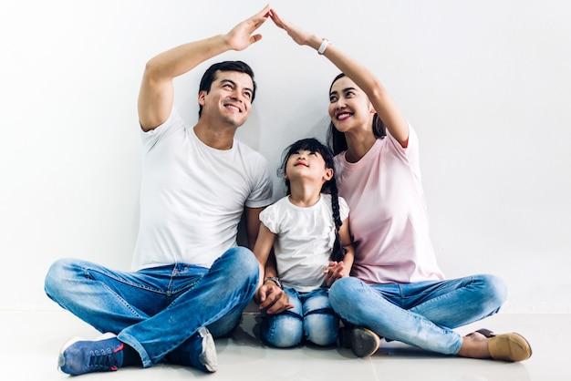 Gelukkige familievader en moeder met dochterzitting en makend dak met handenwapens lucht op muurmuur