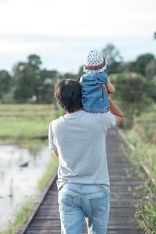 Gelukkige familievader met baby op zijn schouder.