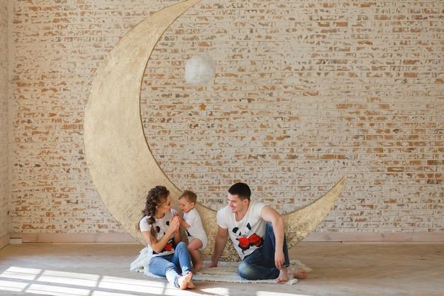 Gelukkige familievader, moeder en kindzoon dichtbij een lege bakstenen muur in de ruimte.