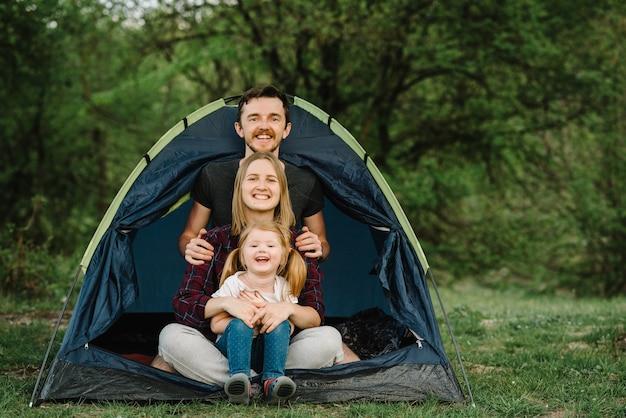 Gelukkige familievakantie in een tent met een kind in de natuur. ð¡ concept van zomervakantie en reizen, reis. camping. mama, papa knuffelt een kind en geniet van een kampeervakantie op het platteland.