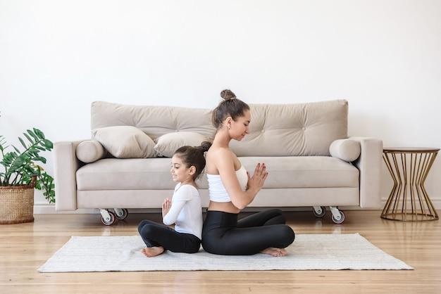 Gelukkige familievrouw en kind brengen tijd samen door thuis yoga te doen