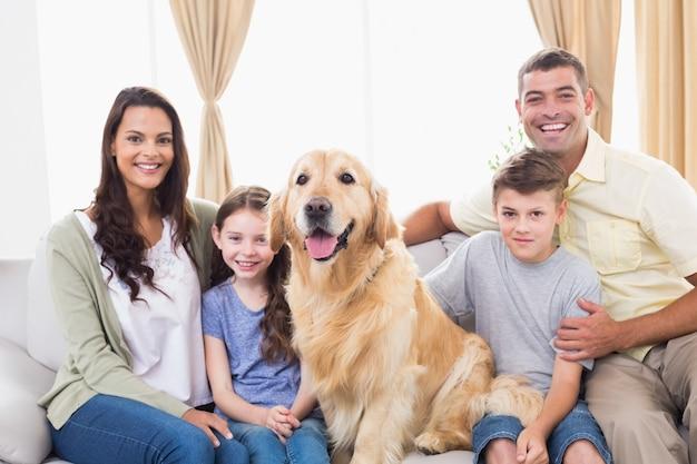 Gelukkige familiezitting met golden retriever op bank
