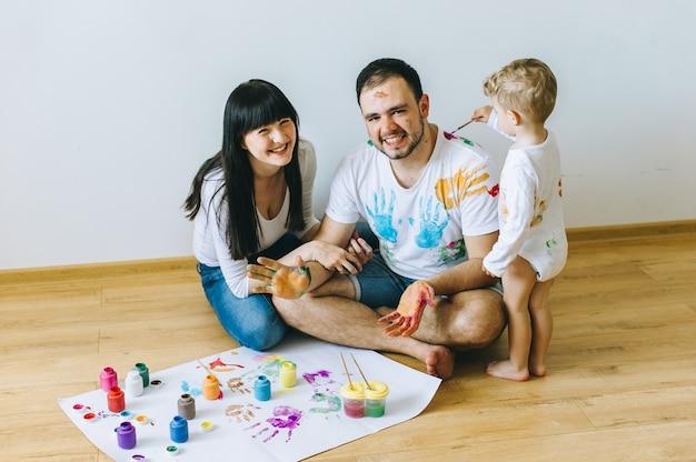 Gelukkige familiezoon met ouders en een kat die een affiche en een andere met verven schilderen