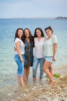 Gelukkige familiezusters die in de zomer op een houten ponton voor de zee staan.