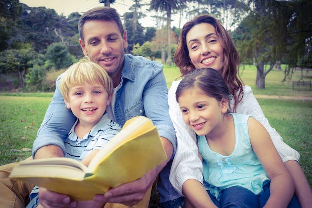 Gelukkige familly die een boek in het park leest