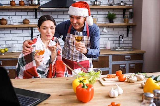 Gelukkige feestelijke man en vrouw in keuken.