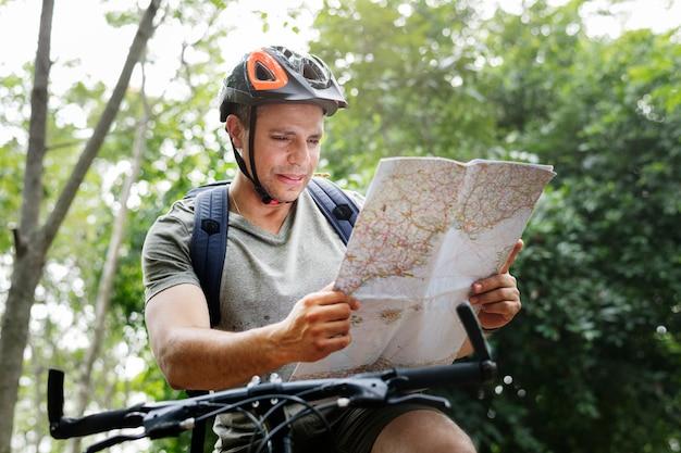 Gelukkige fietser die door het bos berijden