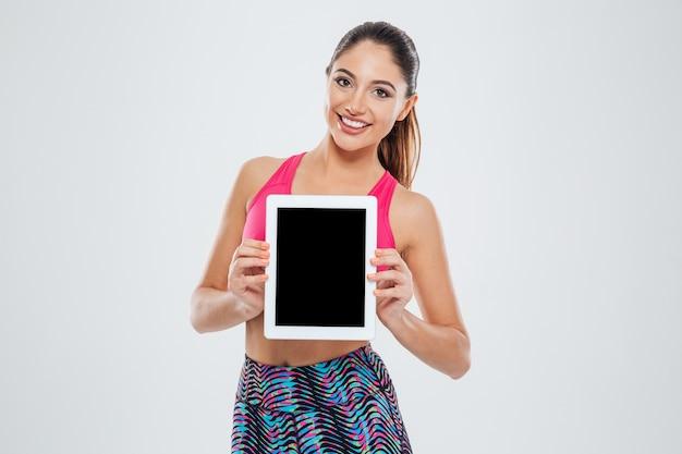 Gelukkige fitnessvrouw die het lege scherm van de tabletcomputer toont