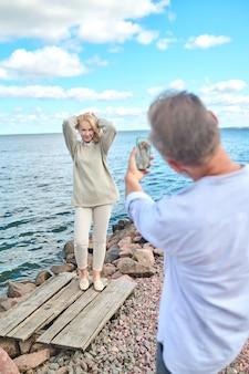 Gelukkige foto. man met rug naar camera met smartphone die een vrolijke poserende vrouw met opgeheven handen in de buurt van zee fotografeert