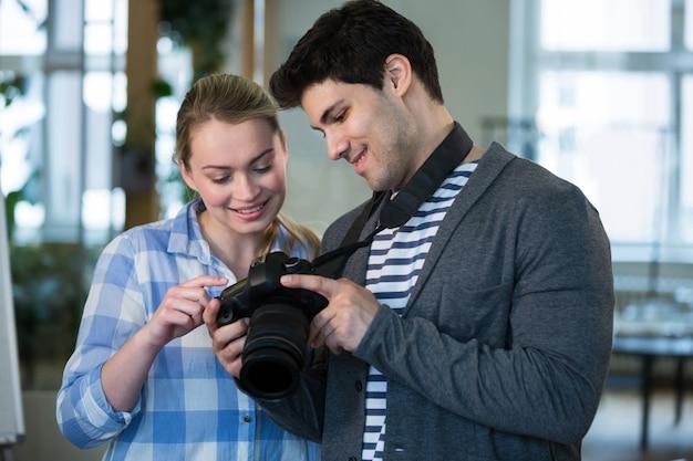 Gelukkige fotograaf die beeld tonen aan collega op creatief kantoor