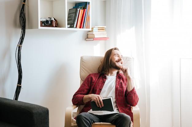 Gelukkige gebaarde jonge mens met boekzitting op leunstoel en thuis het bekijken het venster