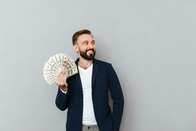 Gelukkige gebaarde mens in bedrijfskleren die geld houden en weg over grijs kijken