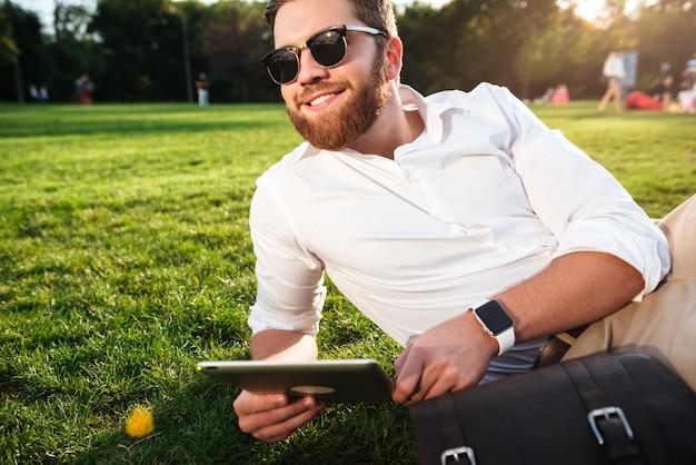 Gelukkige gebaarde mens in op gras in openlucht met tabletcomputer liggen en zonnebril die weg eruit zien