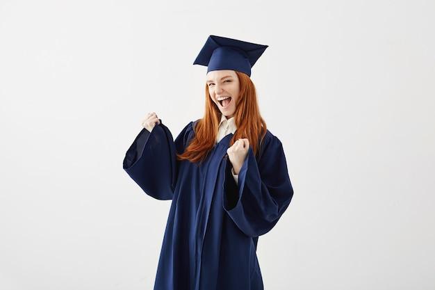 Gelukkige gediplomeerde vrouw in mantel het verheugen het lachen glimlachen.