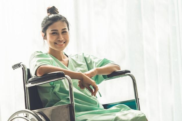 Gelukkige geduldige zitting op rolstoel in het ziekenhuis. medische gezondheidszorg achtergrond.