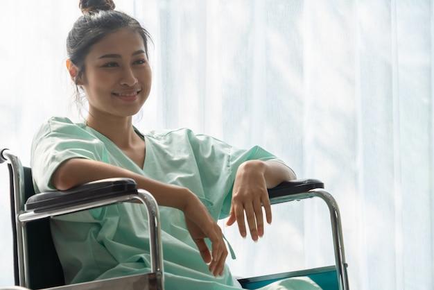Gelukkige geduldige zitting op rolstoel in het ziekenhuis. medische gezondheidszorg concept.
