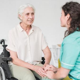 Gelukkige gehandicapte verpleegsterszitting op wielstoel die thuisbewaarder bekijken