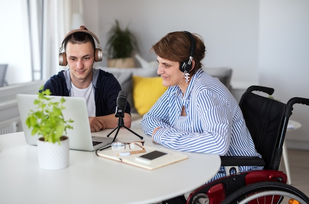 Gelukkige gehandicapten die thuis aan tafel zitten en thuis podcasts opnemen.